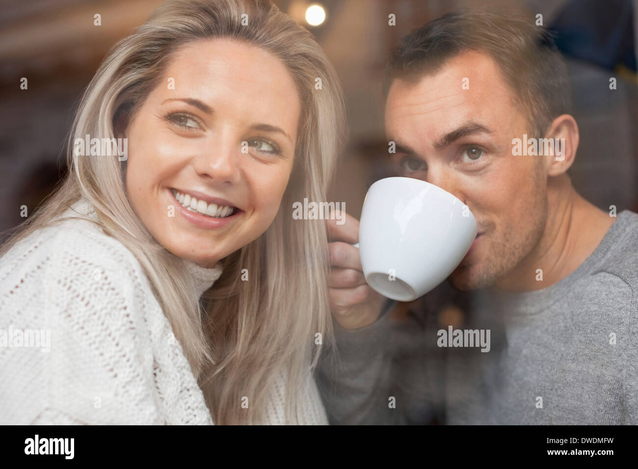 Happy couple looking out of cafe window - Stock Image