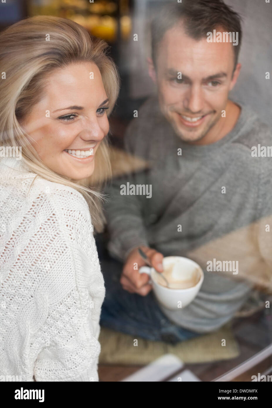 Happy couple looking out of cafe window while having coffee - Stock Image