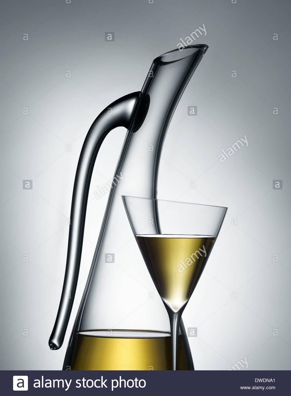 translucent image of a contemporary wine carafe and glass with golden white wine against light gray background - Stock Image