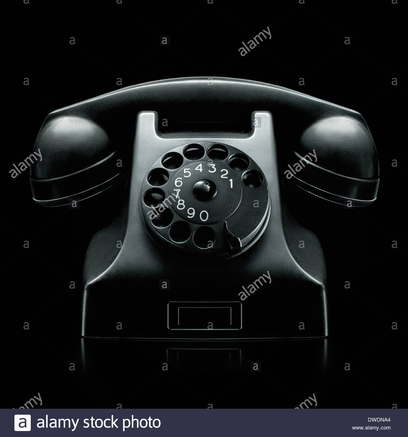 old vintage rotary dial black telephone photographed on very moody dark black background - Stock Image
