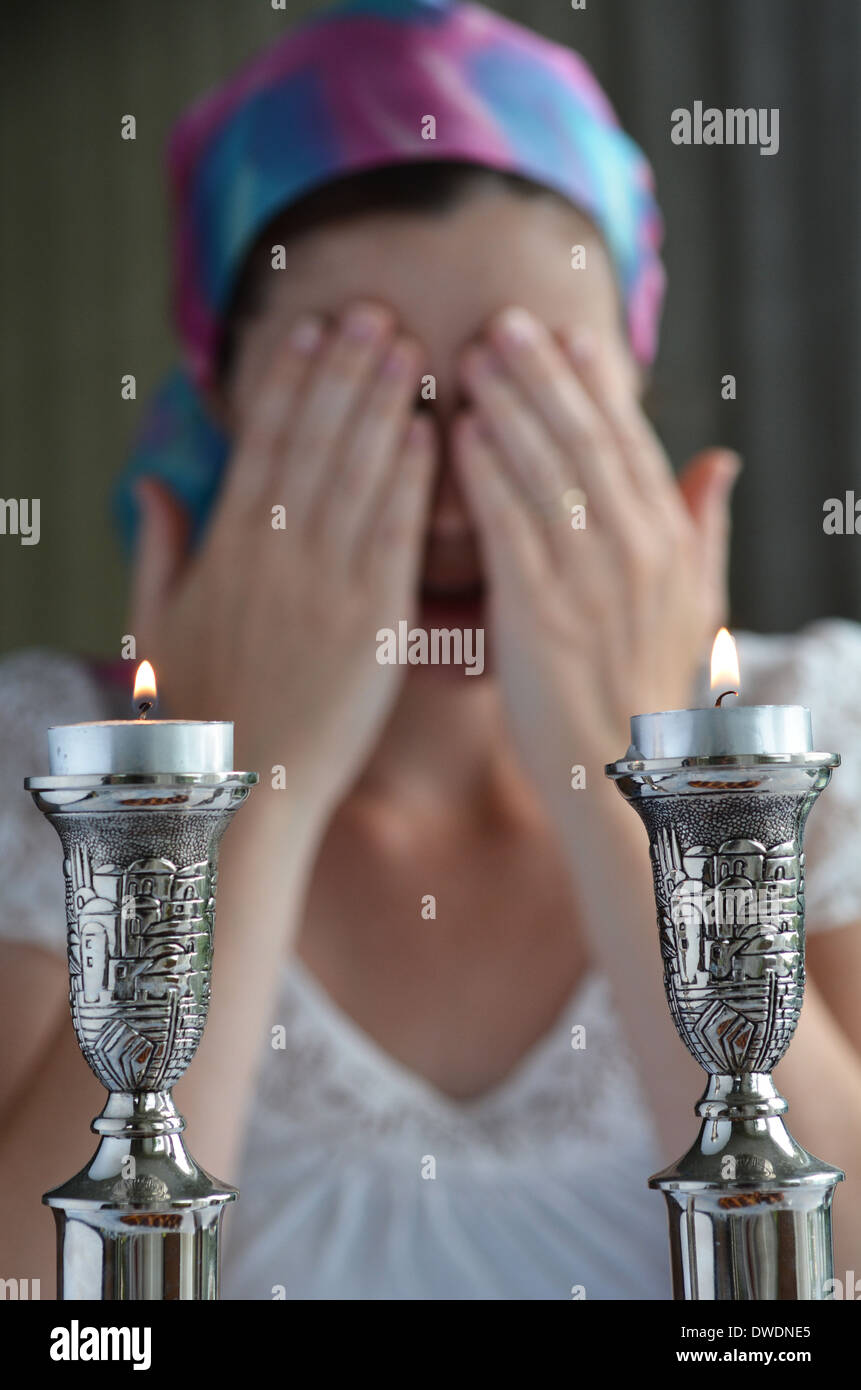 Jewish woman says the blessing upon lighting the sabbath candles before shabbat eve dinner. - Stock Image