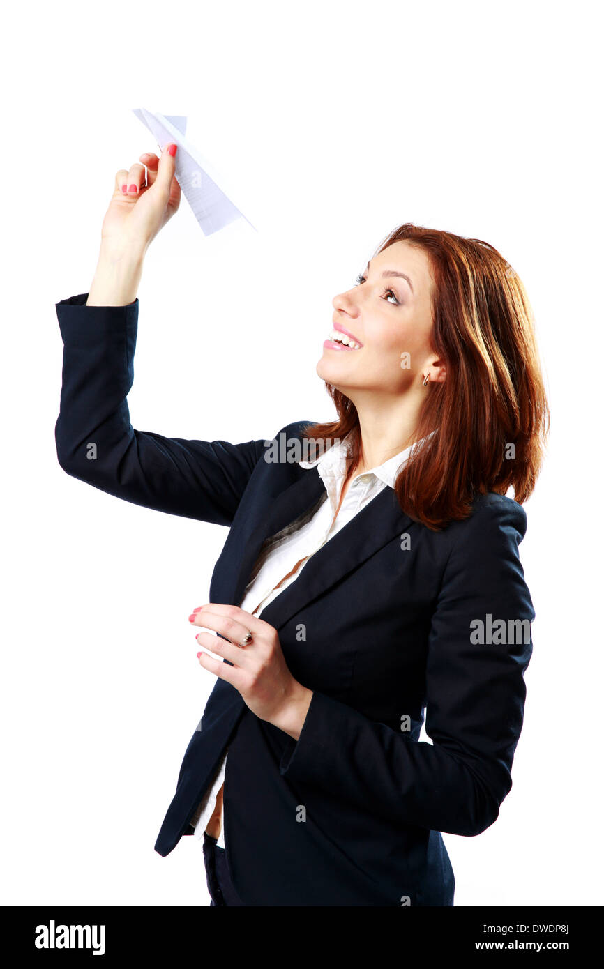 Smiling businesswoman throwing paper plane isolated on a white background - Stock Image