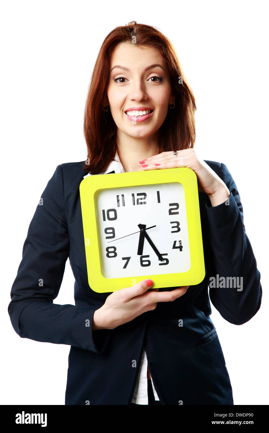 Happy businesswoman holding wall clock isolated on white background - Stock Image