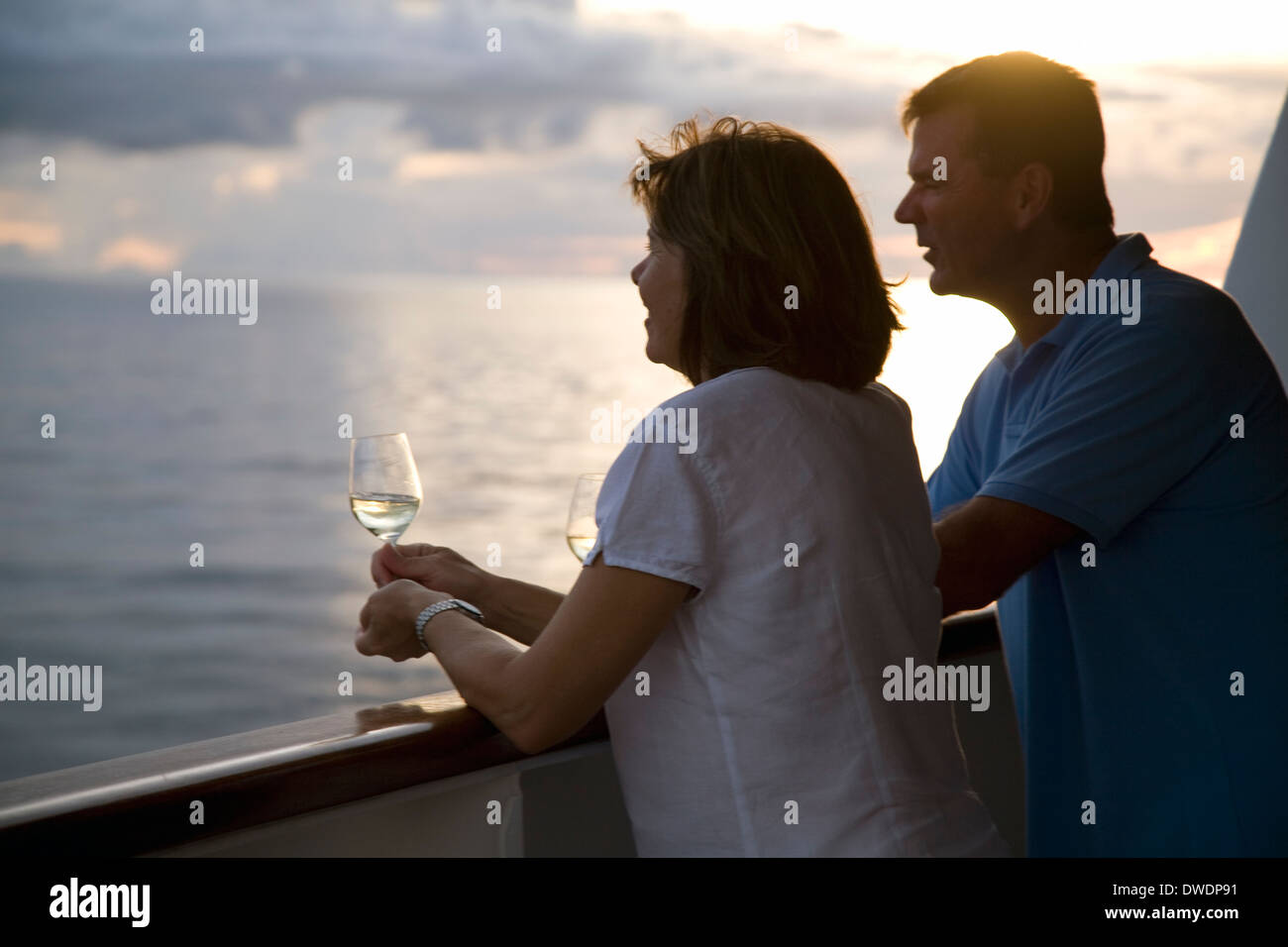 Couple toasts perfect day onboard the Aussie luxury/expedition cruiser Orion, at sea in the Solomon Islands. - Stock Image
