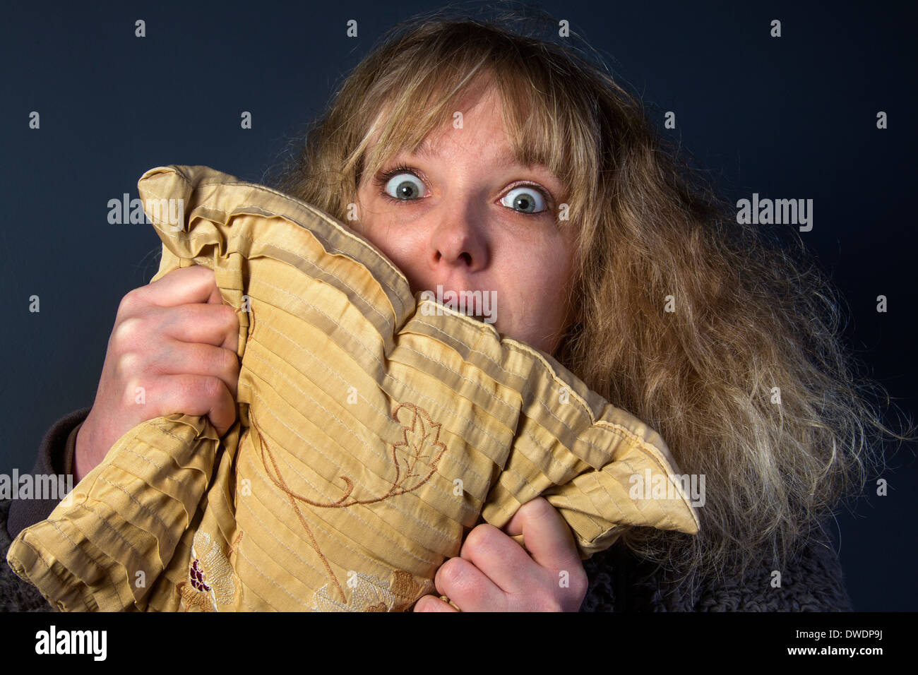 A frightened young woman watching a horror movie Stock Photo