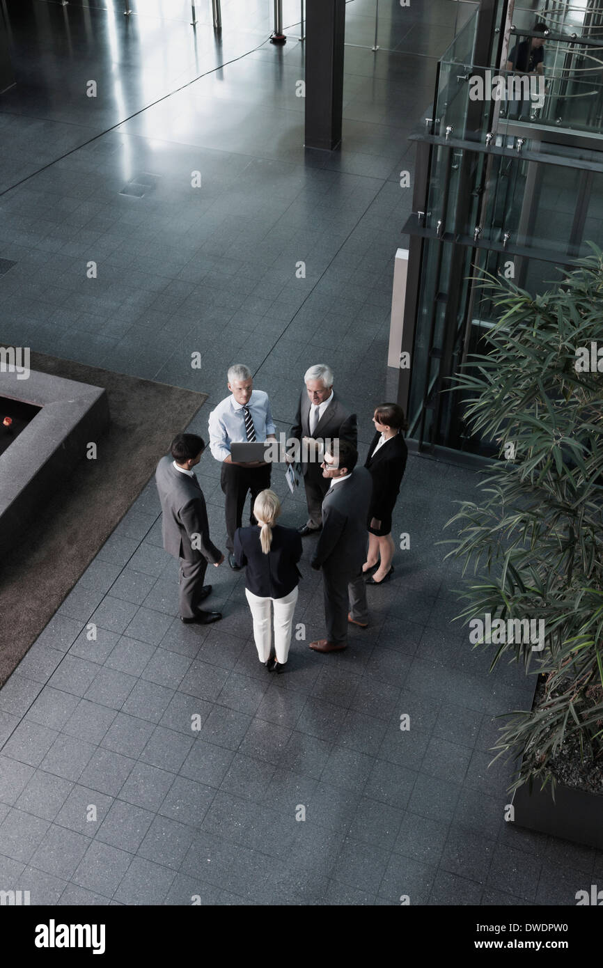 Group of businesspeople with laptop talking in lobby - Stock Image