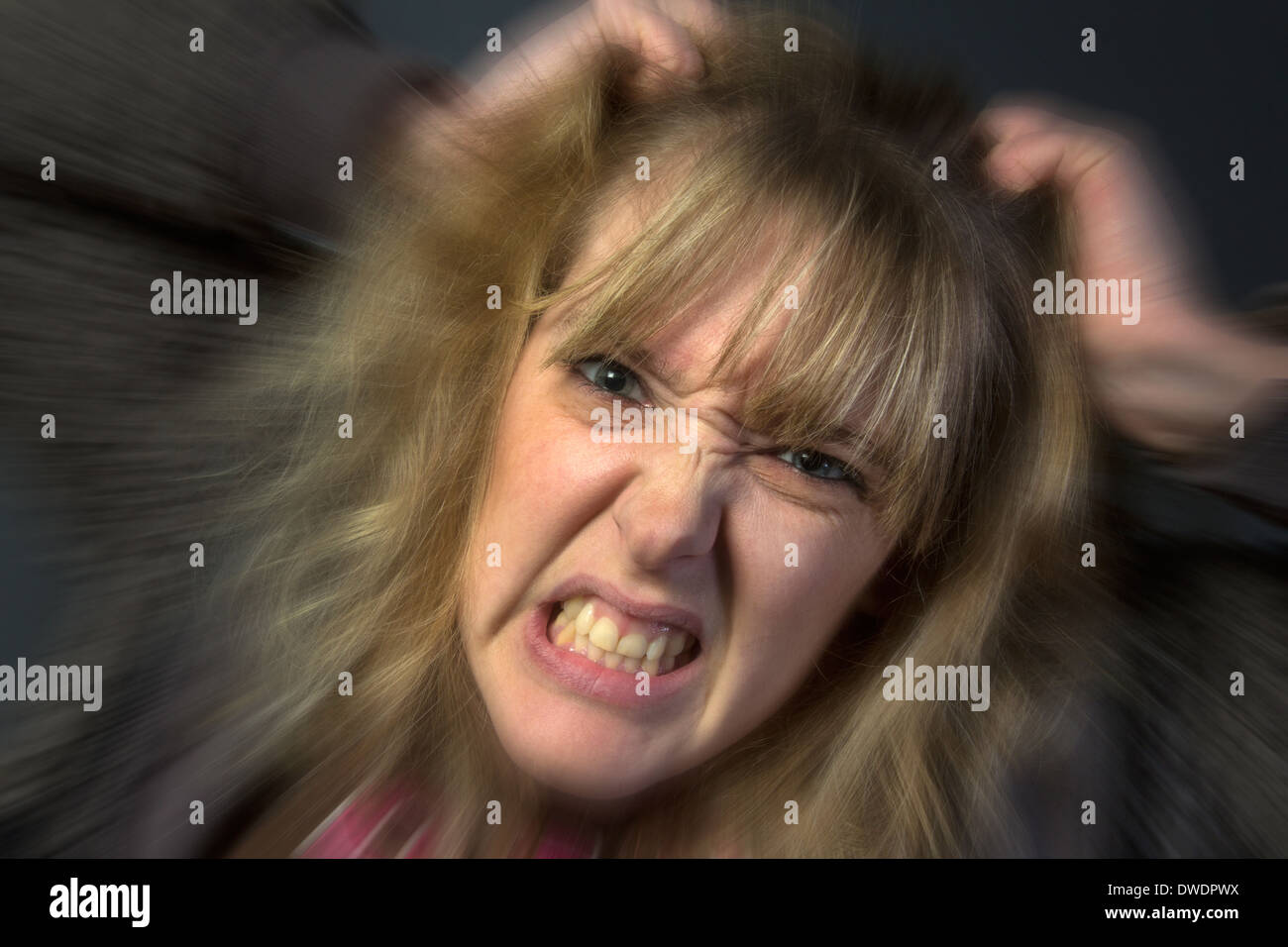 A very angry young woman tearing her hair out. - Stock Image