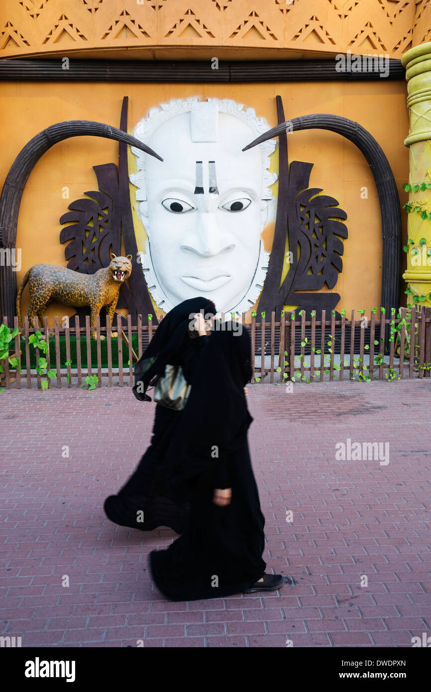 Women walk past Africa Pavilion at Global Village tourist cultural attraction in Dubai United Arab Emirates - Stock Image