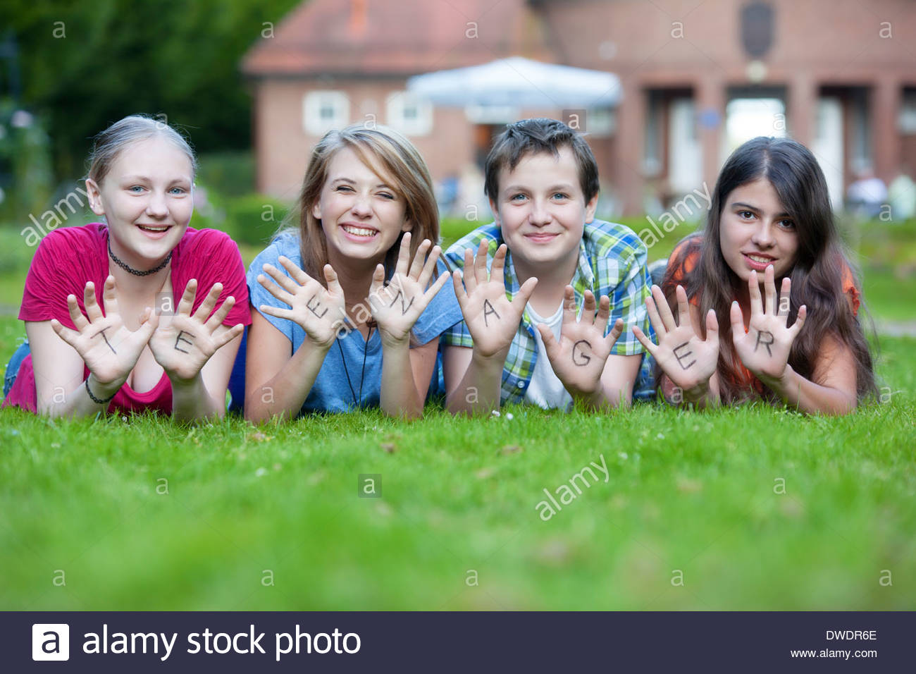 Three girls and one boy showing together the word teenager on their palms - Stock Image