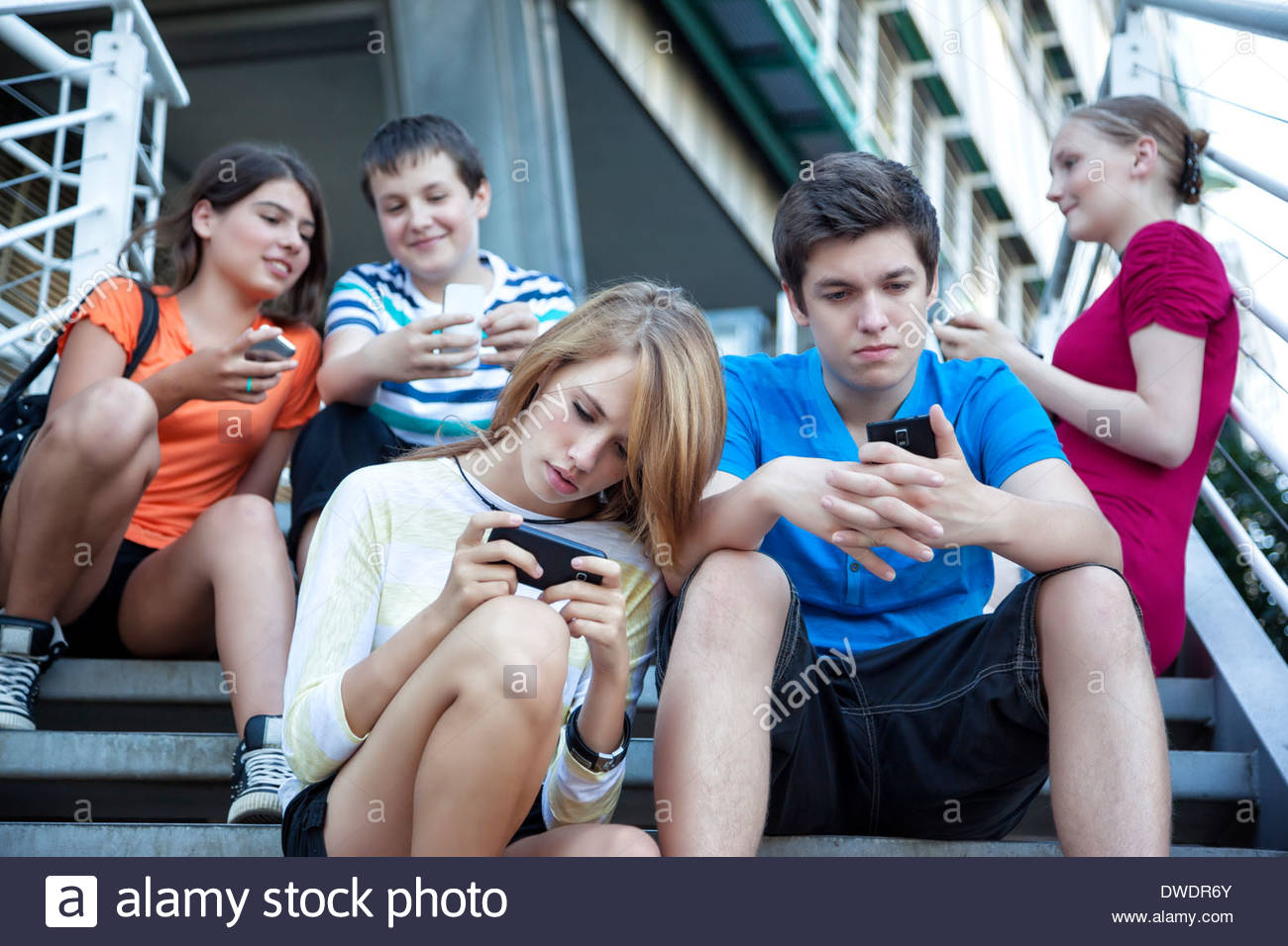 Teenage friends using mobile devices on stairs - Stock Image