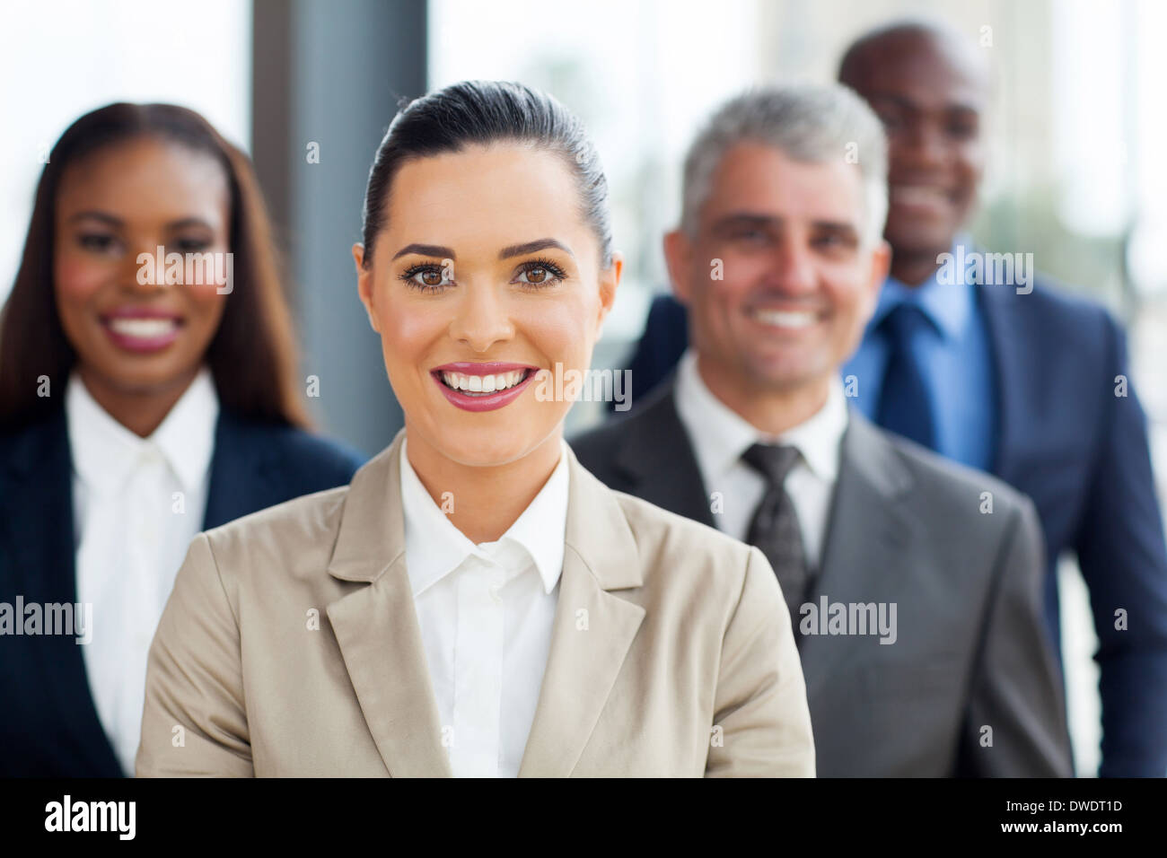 cute businesswoman standing with co-workers in office - Stock Image