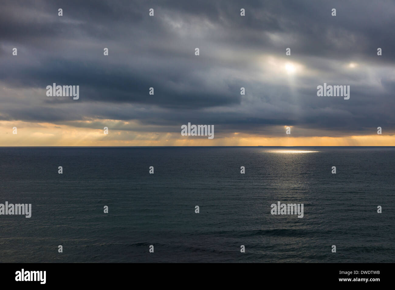 Sunrays slipping through the clouds over a calm ocean - Stock Image