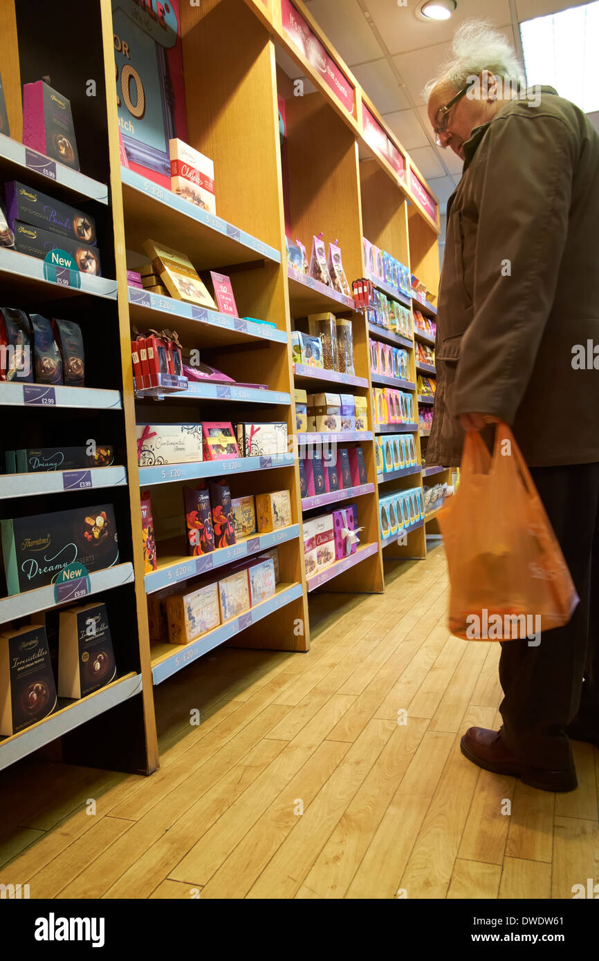 An elderly senior man browsing looking at boxes of thornton's chocolates England uk - Stock Image