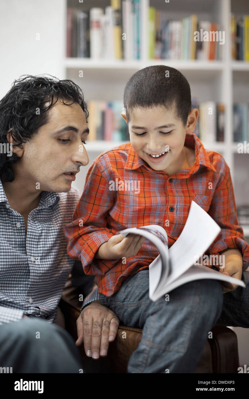 Father assisting son in doing homework at home - Stock Image