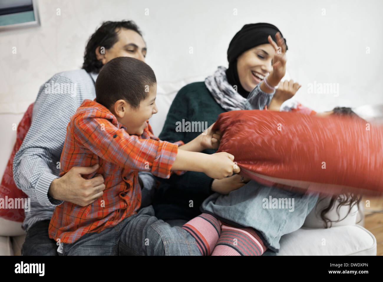 Playful Muslim family in living room - Stock Image