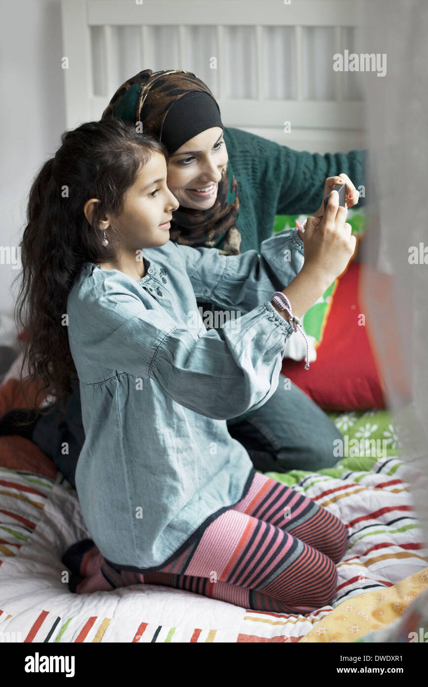 Mother and daughter photographing in bedroom - Stock Image