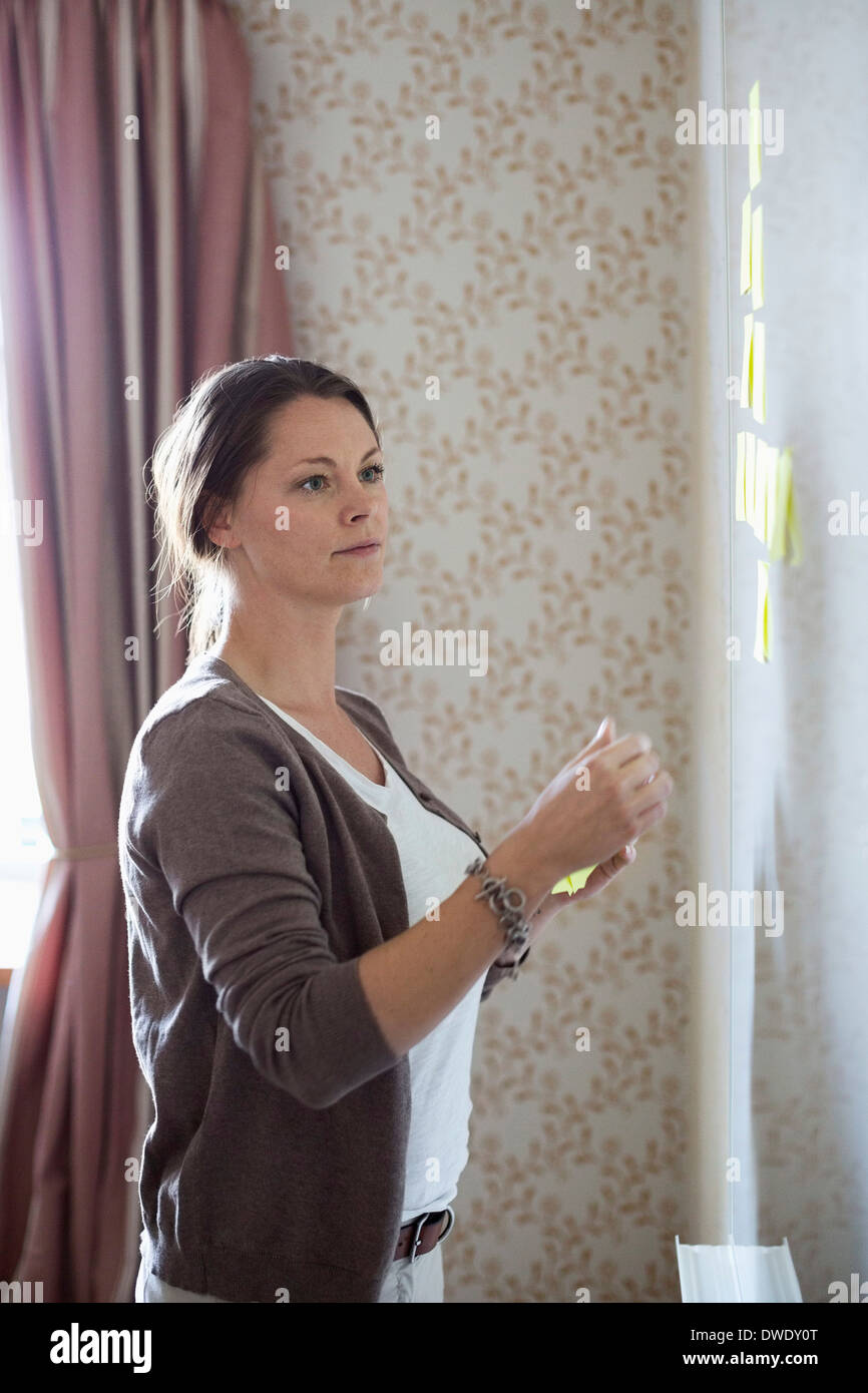 Businesswoman looking at memo notes on whiteboard - Stock Image