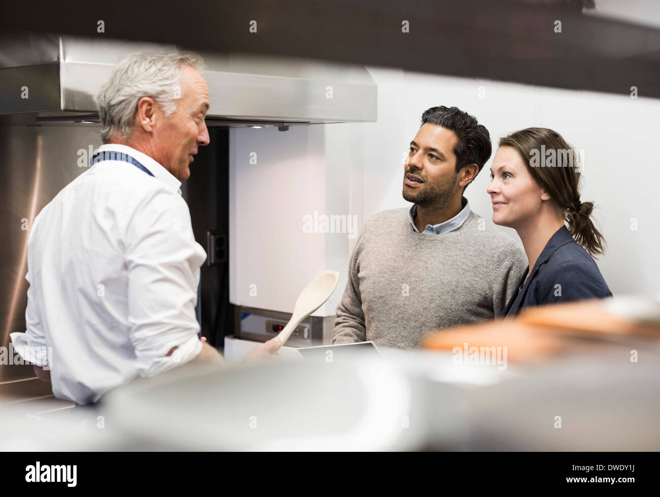 Chef talking to business people in commercial kitchen - Stock Image