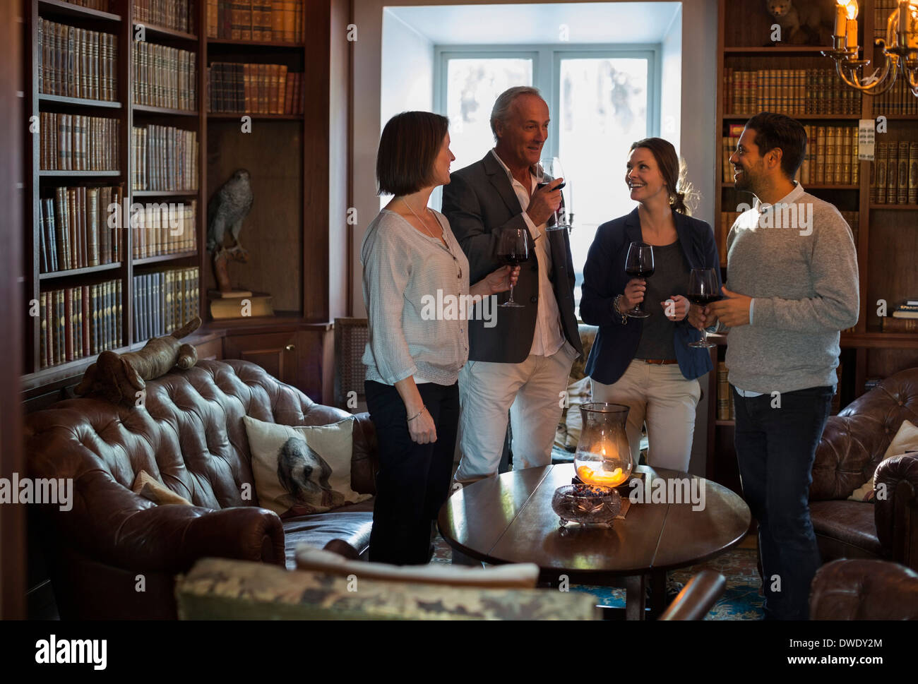 Business people with wineglasses spending leisure time at restaurant lobby - Stock Image