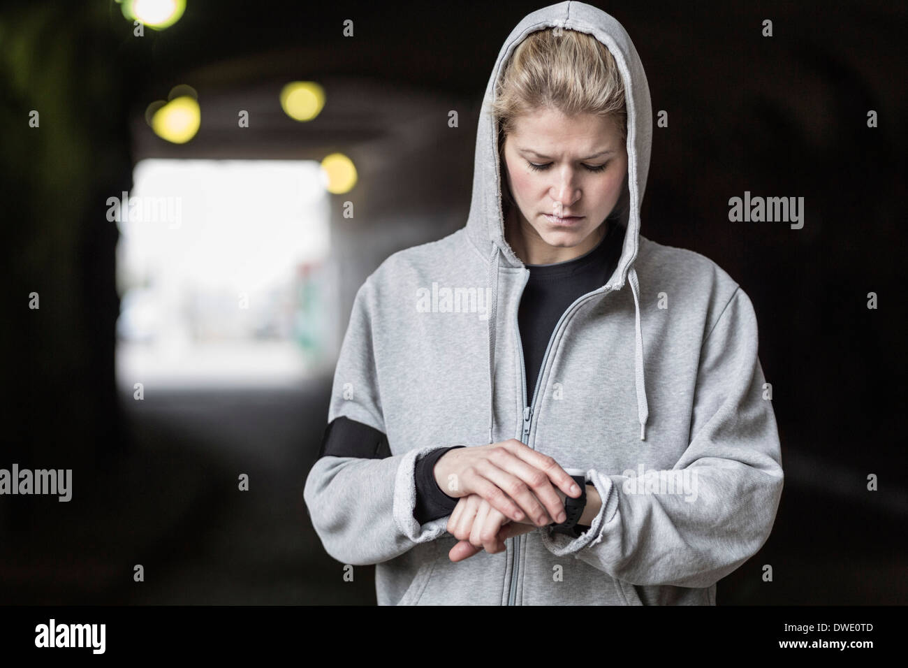 Female jogger checking time in tunnel Stock Photo