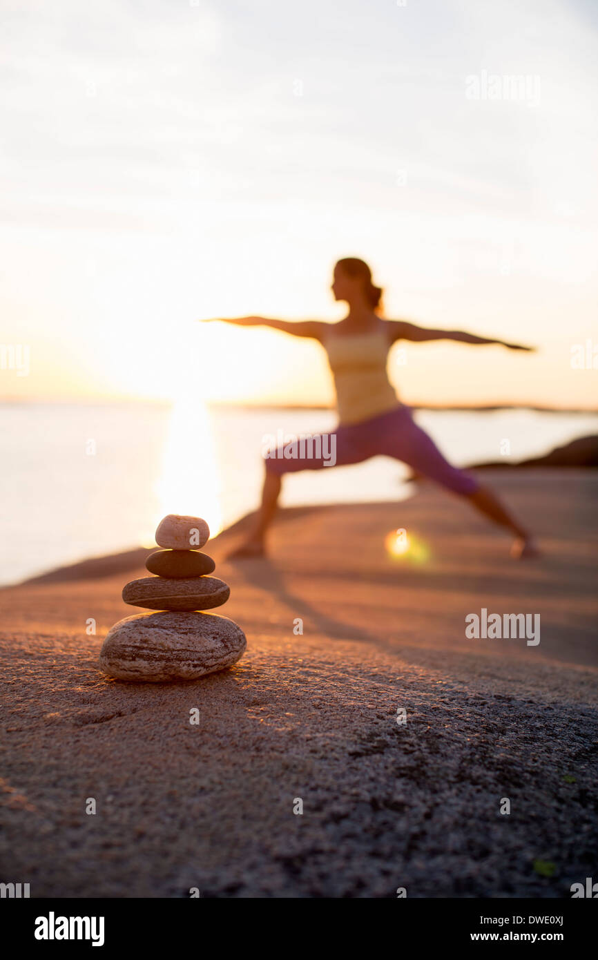 Woman practicing yoga warrior pose on lakeshore with focus on stack of stones - Stock Image