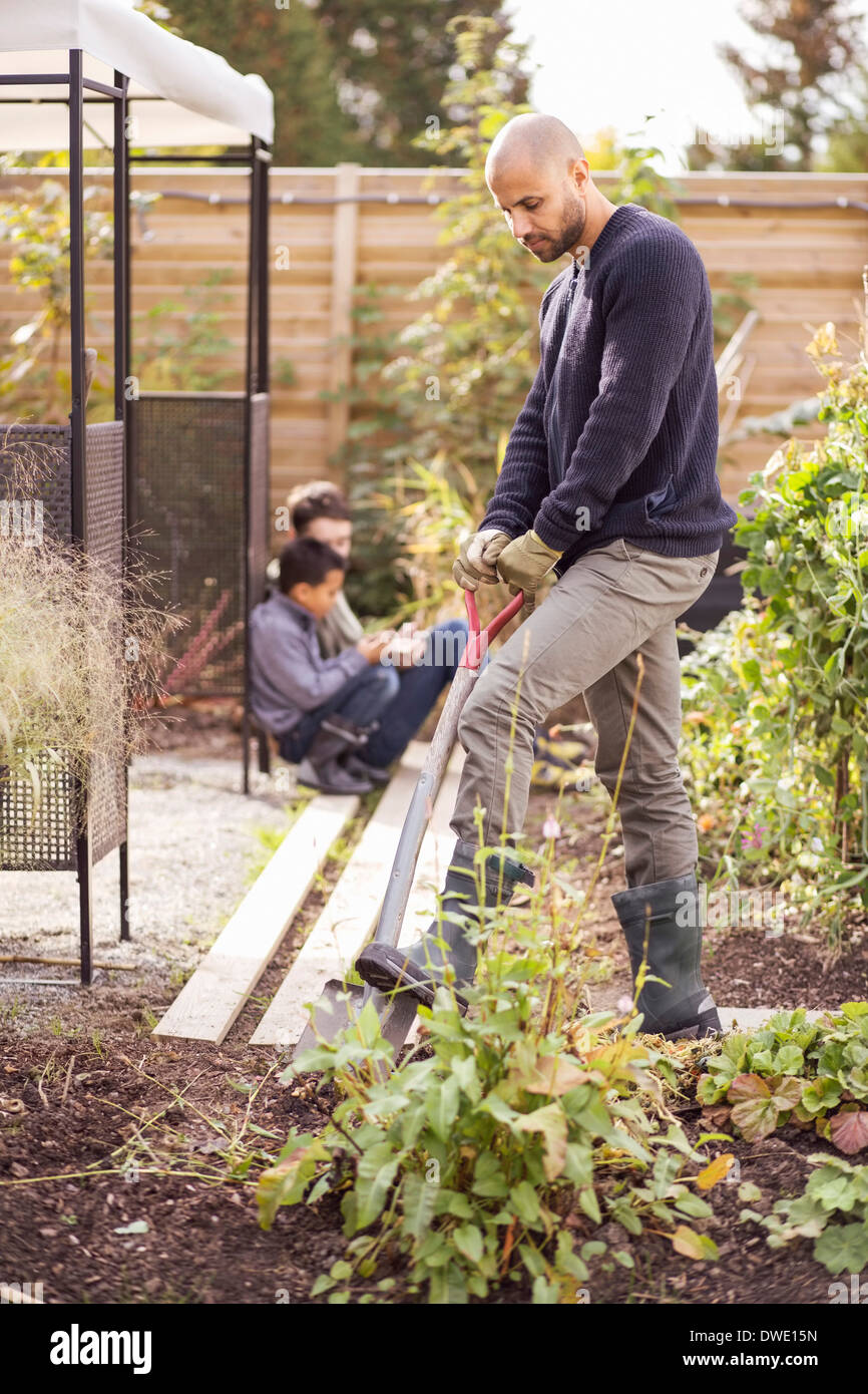 Man digging in garden with children in background - Stock Image