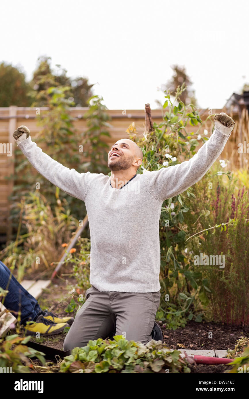 Mature man with arms outstretched in garden - Stock Image