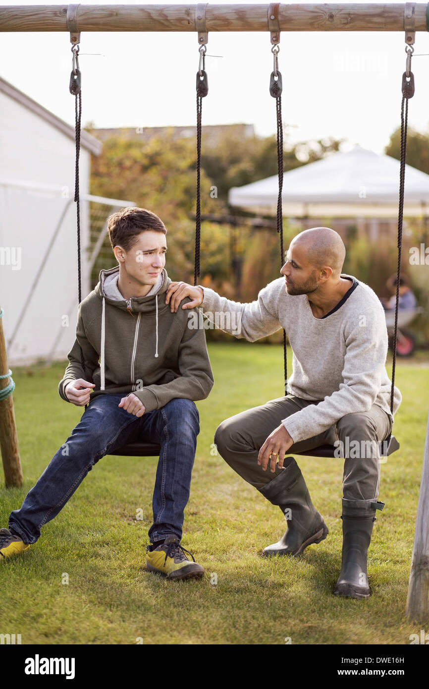 Father and son sitting on swings in garden - Stock Image