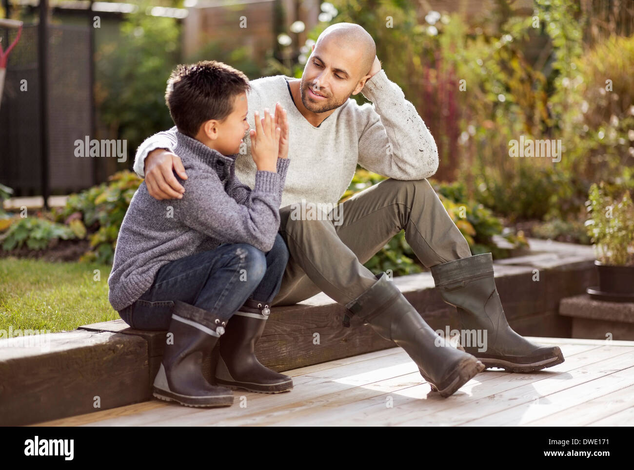 Father and son sitting in garden - Stock Image