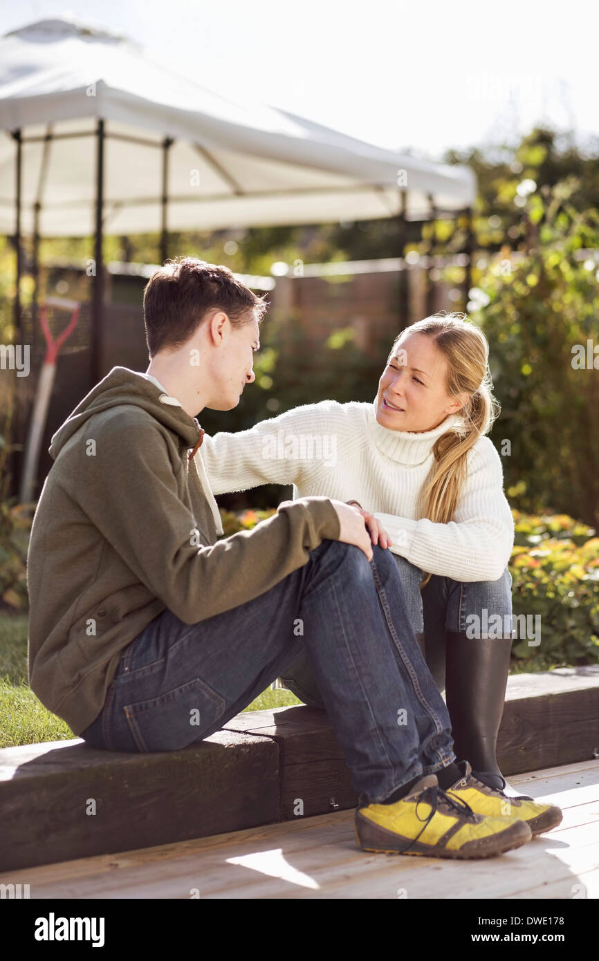 Mother and son talking while sitting in garden - Stock Image