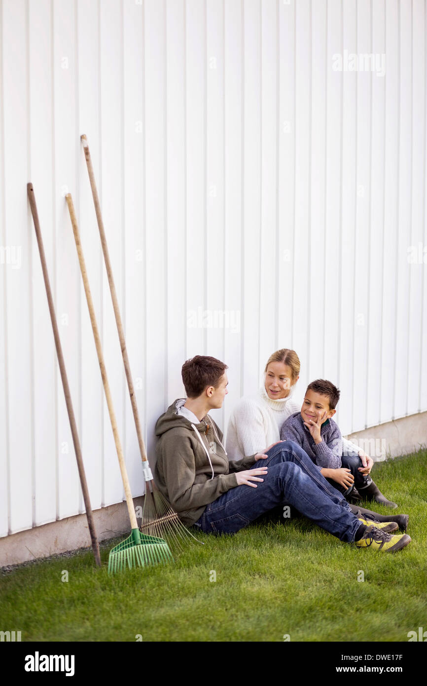 Mother and sons with gardening equipment sitting at yard - Stock Image