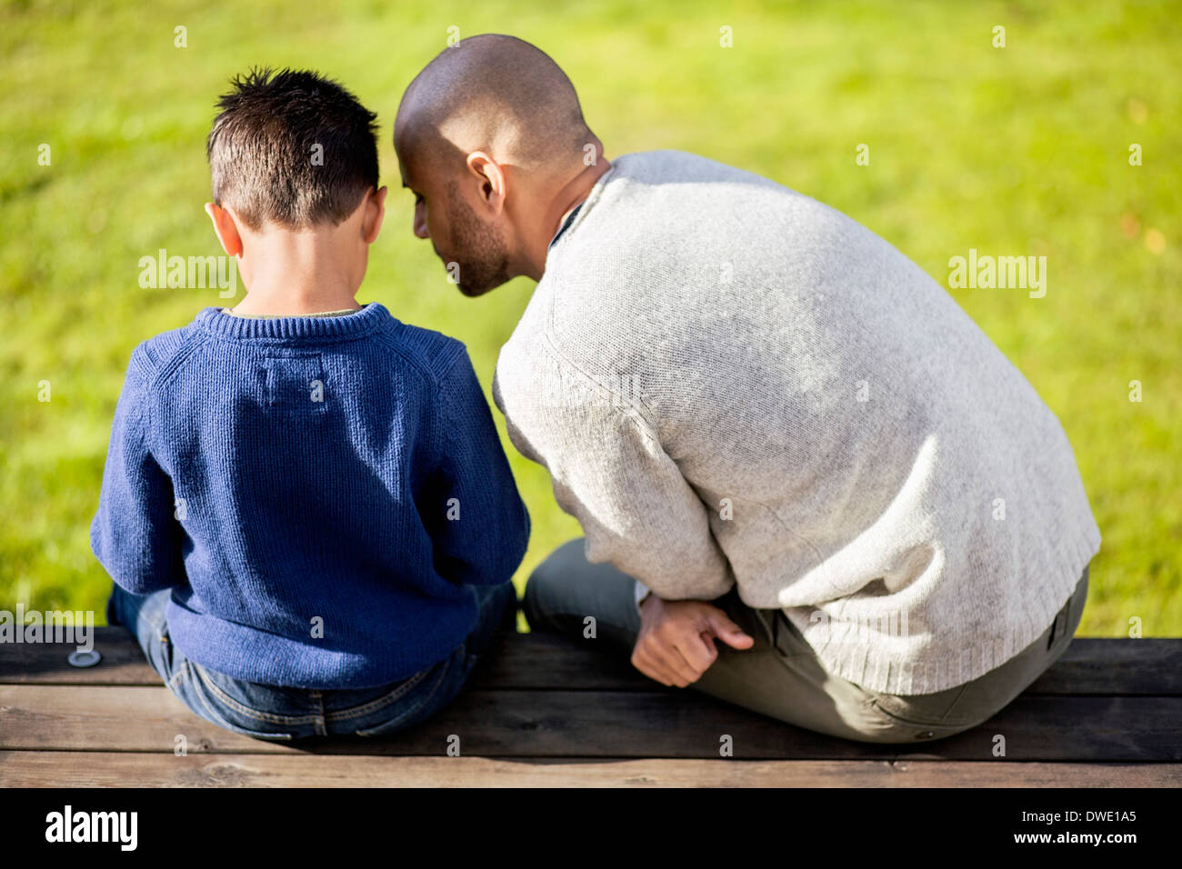 Rear view of father and son sitting at yard Stock Photo