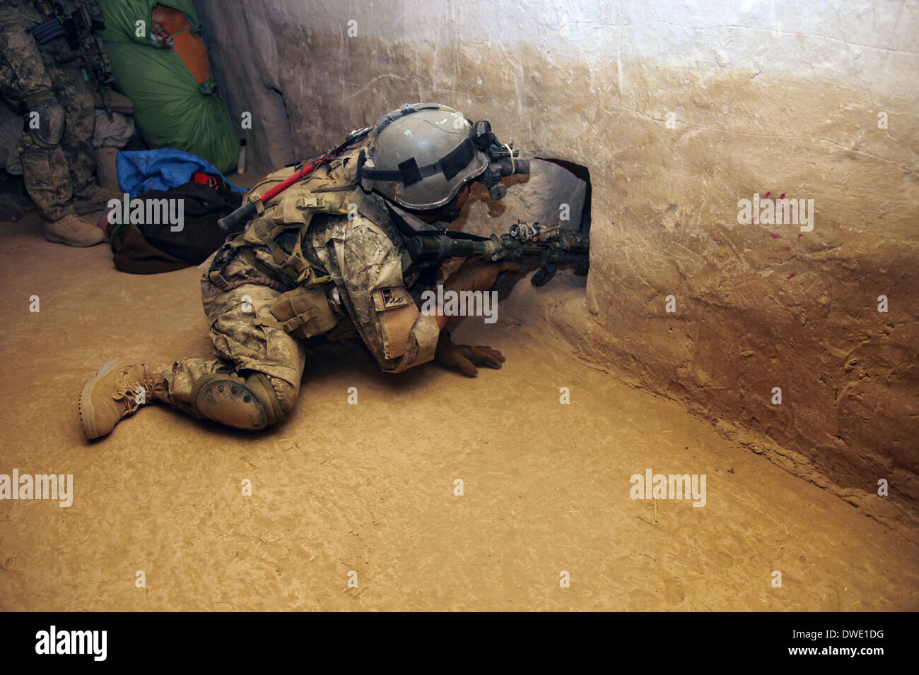 An Afghan soldier searches a crawl space for suspected insurgents during an operation to detain a Taliban weapons Stock Photo