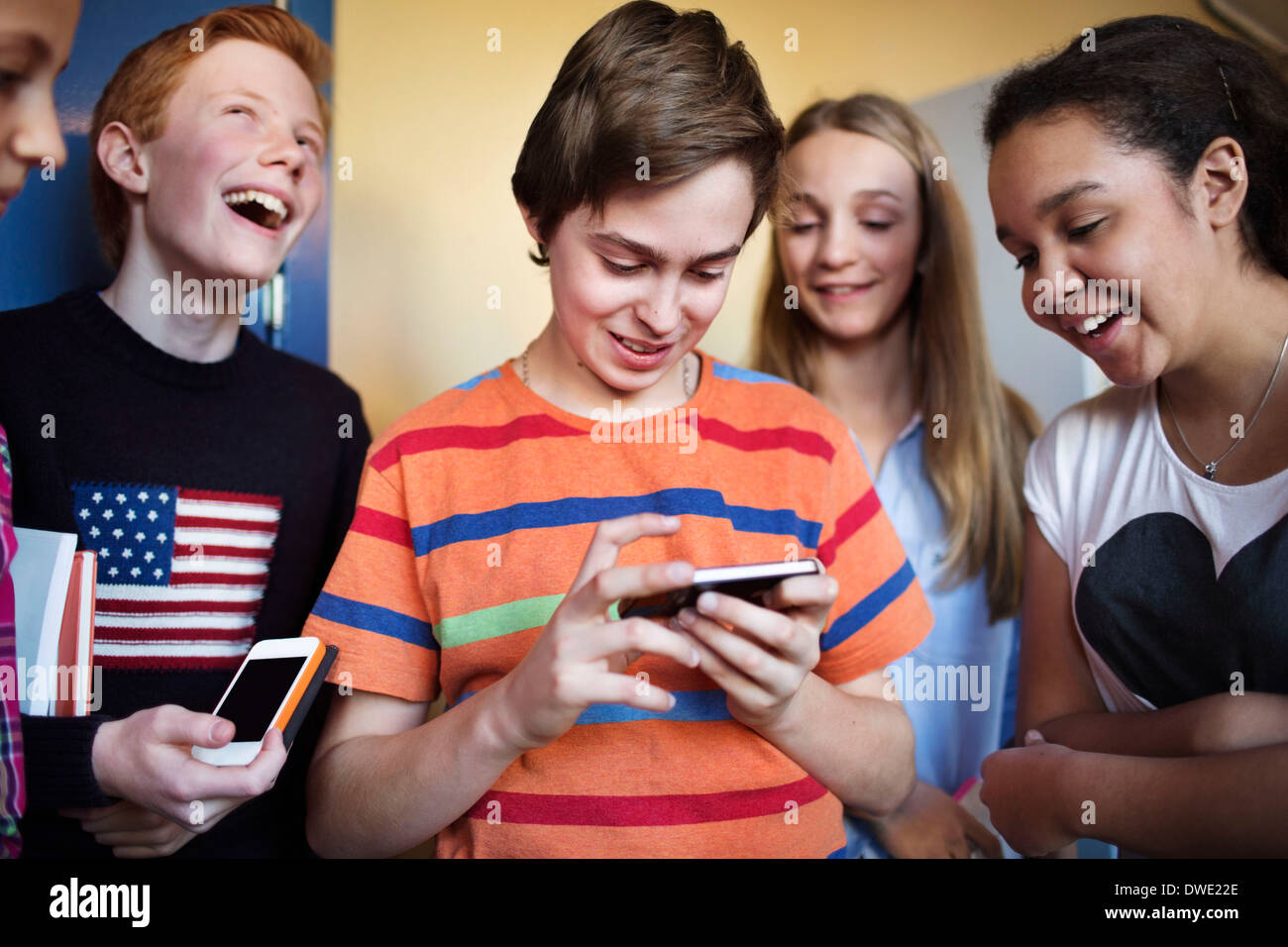 Happy students using cell phones in high school - Stock Image