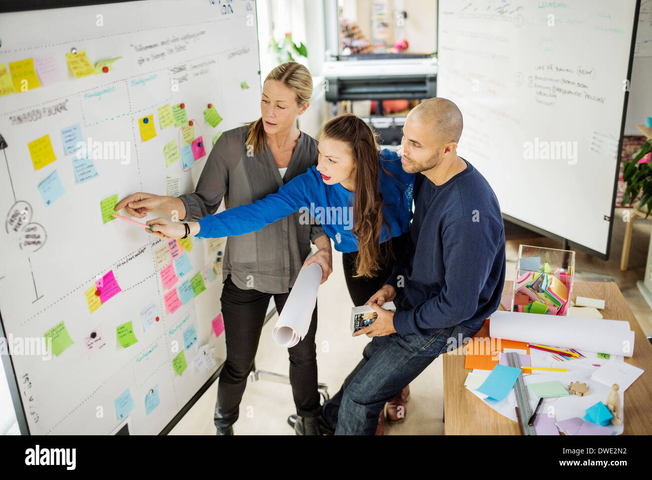 Business people reading reminder in creative office - Stock Image