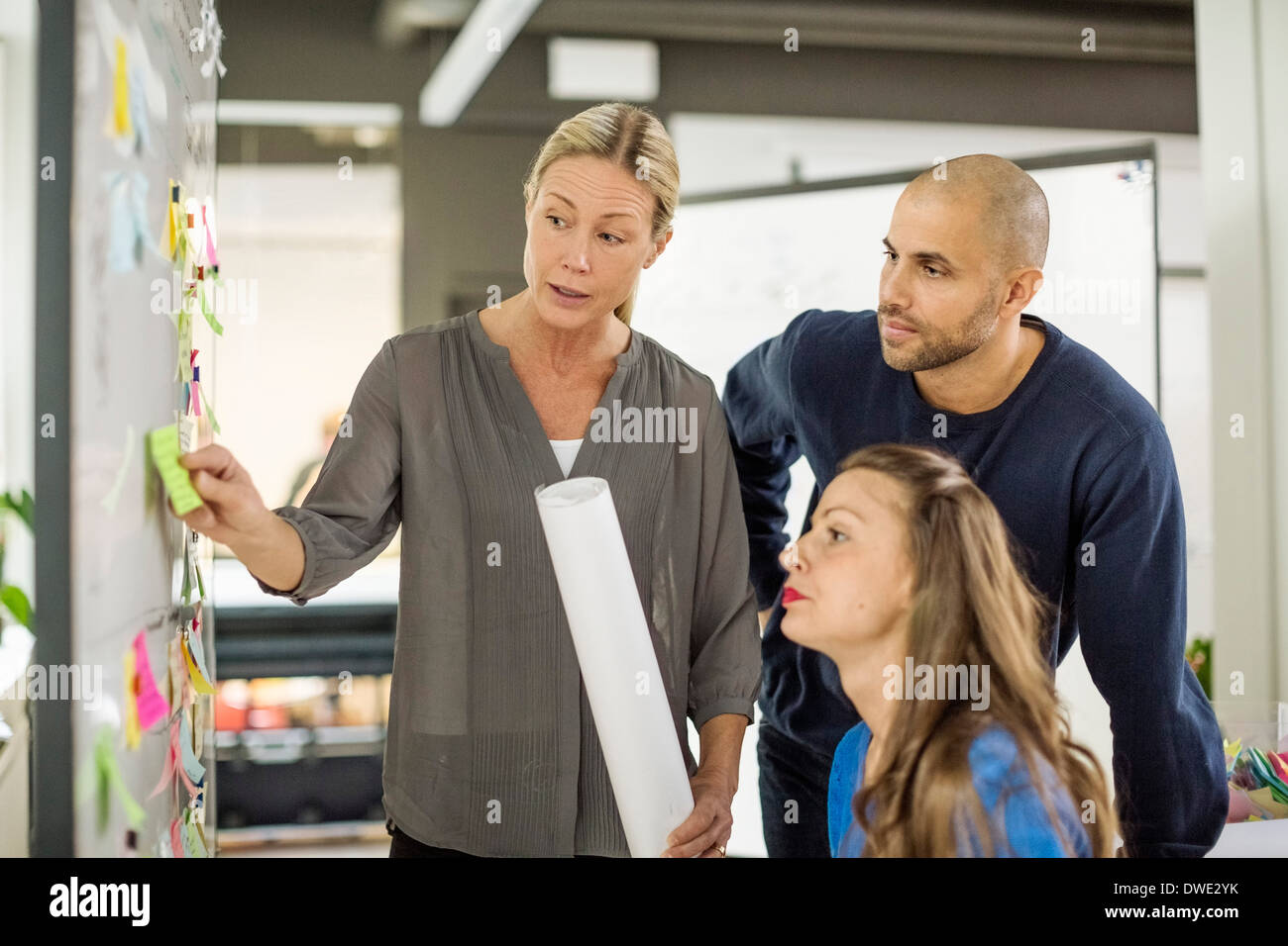 Business people discussing about reminder in creative office - Stock Image