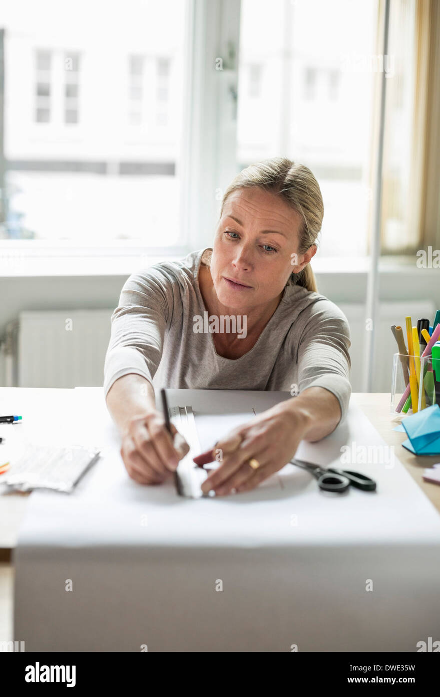 Mature businesswoman drawing line using ruler on paper - Stock Image