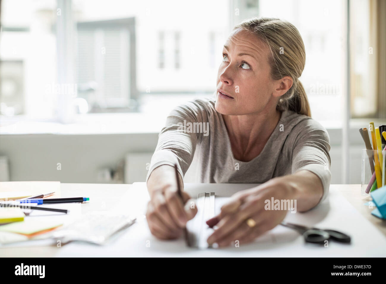Businesswoman drawing line using ruler on paper while looking away - Stock Image