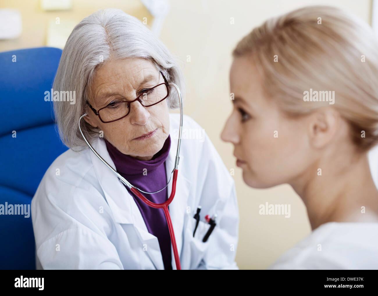 Senior female doctor examining patient in clinic - Stock Image