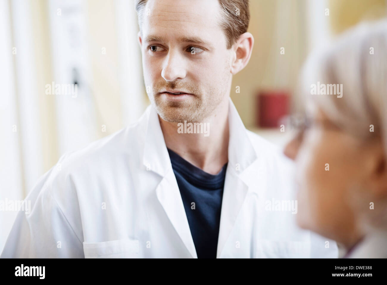 Mid adult male doctor with female colleague in hospital - Stock Image