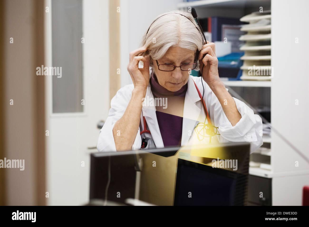 Senior female audiologist wearing headphones in examination room - Stock Image
