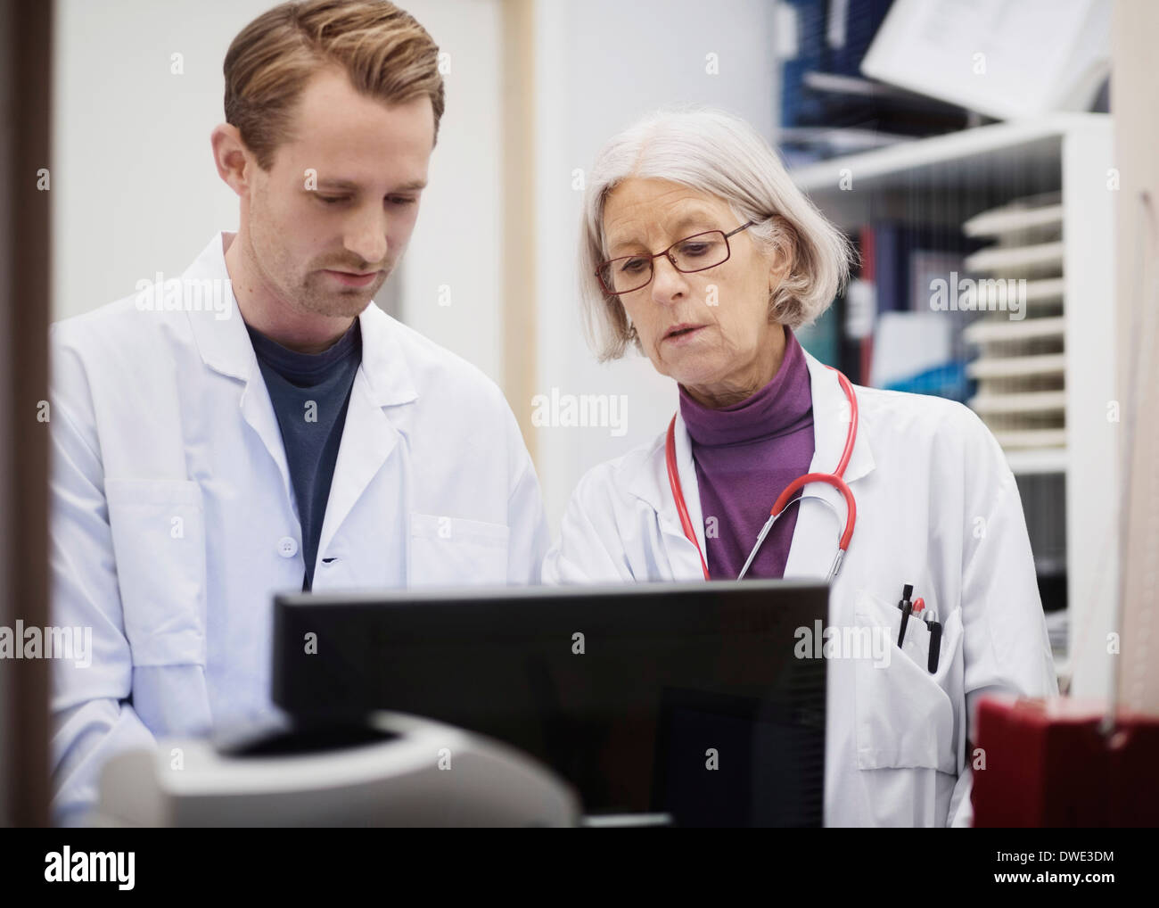 Senior female doctor with male colleague using computer in examination room - Stock Image