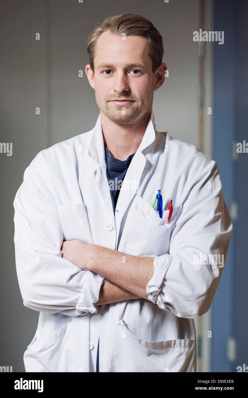 Portrait of confident male doctor with arms crossed in hospital - Stock Image
