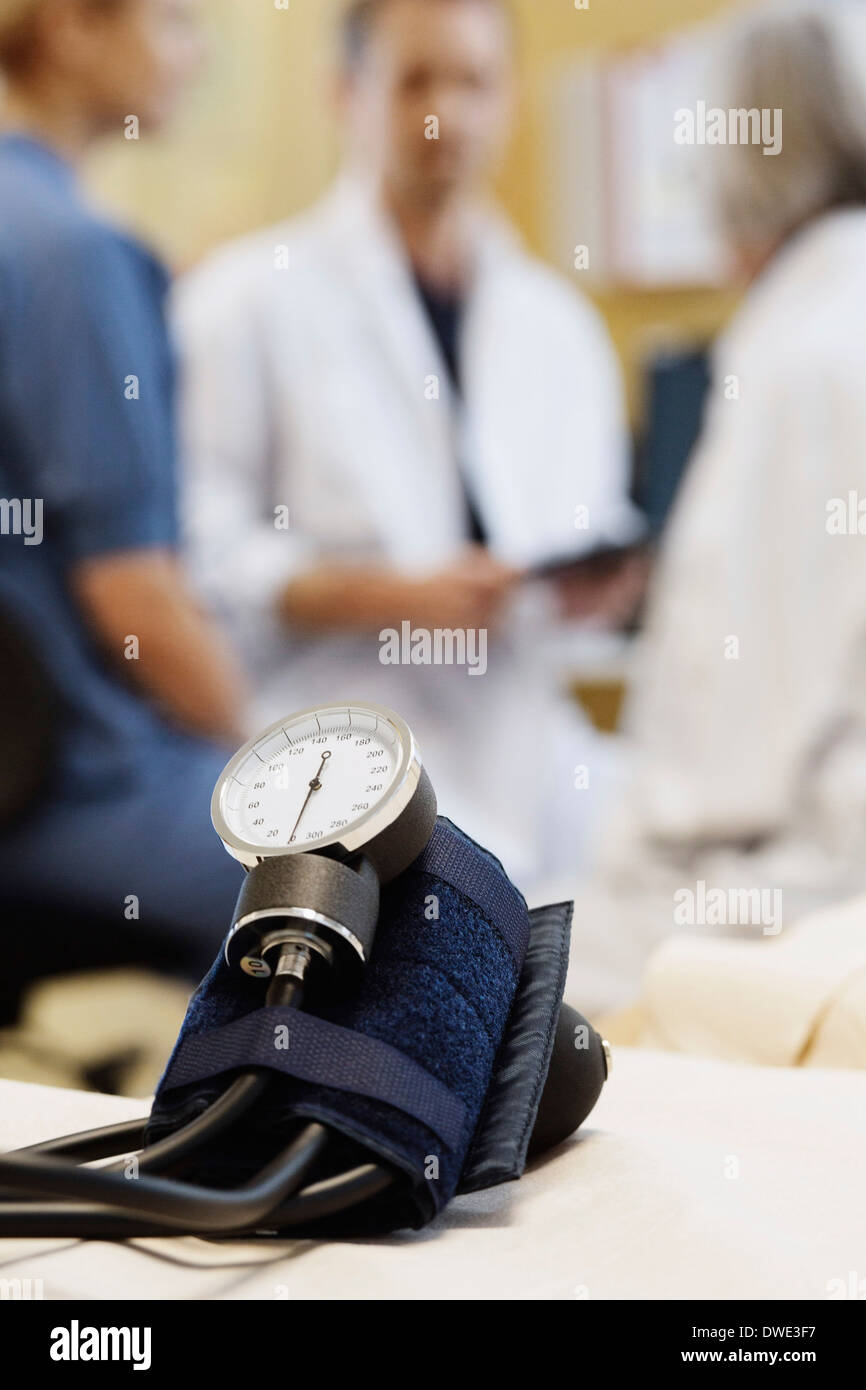 Blood pressure gauge with medical team discussing in background - Stock Image