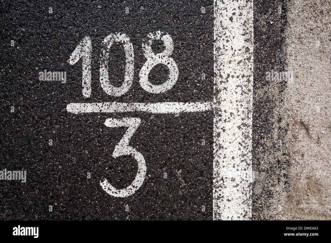 White numbers and digits on the black asphalt - Stock Image