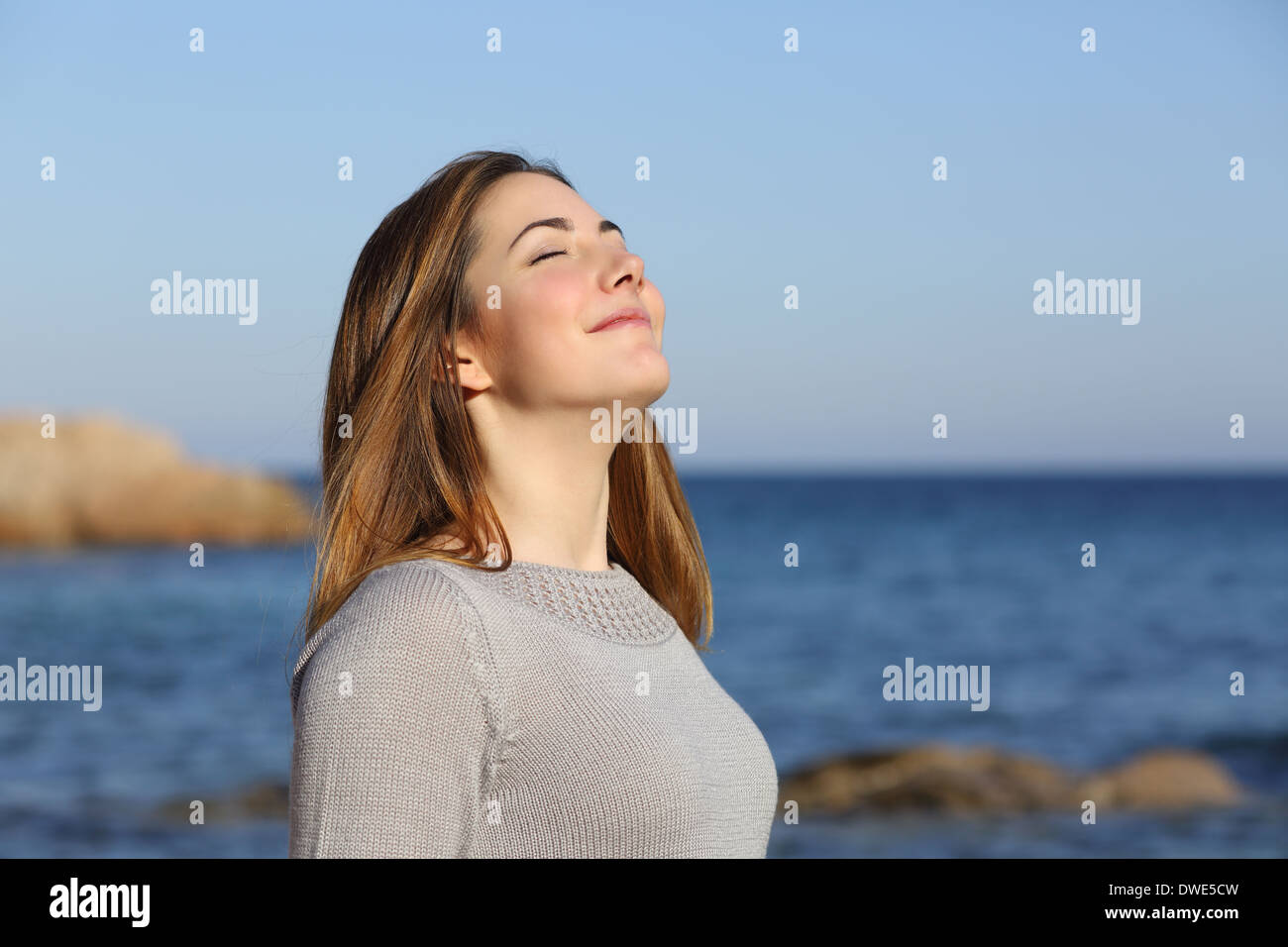 Happy relaxed woman breathing deep fresh air on the beach with the horizon in the background - Stock Image