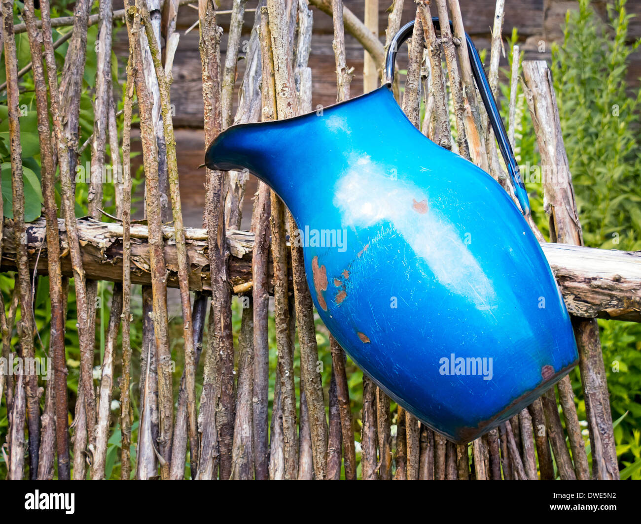 Blue pitcher on a fence - Stock Image