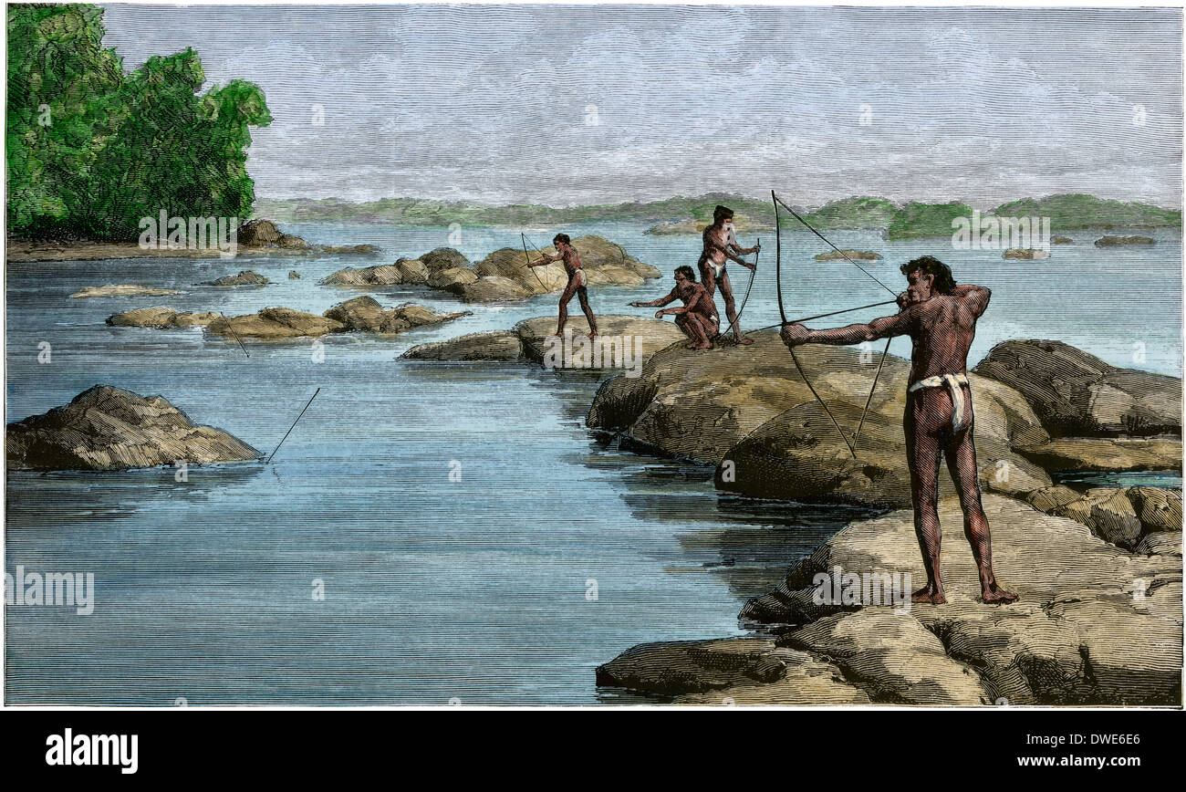 British Guiana natives shooting sting-rays on the Berbice River, 1880s. Hand-colored woodcut - Stock Image
