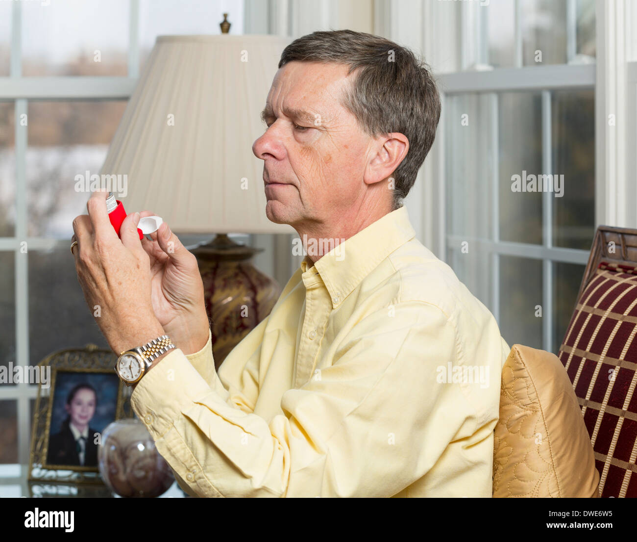 Senior, late middle-aged man at home about to use an asthma inhaler - Stock Image