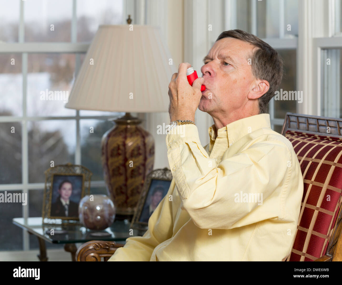 Senior, late middle-aged man at home using an asthma inhaler - Stock Image